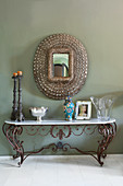 Antique, wrought-iron console table with marble top below mirror on wall