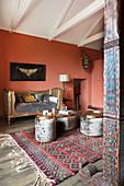 Goldfarbenes, antikes Tagesbett und Beistelltische im Zimmer mit lachsfarbenen Wänden