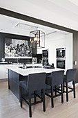 Island counter, fitted appliances and black wall in elegant, open-plan kitchen