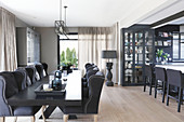 Elegant upholstered chairs around black table in dining area with display cabinet and island counter in background