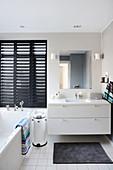 Elegantes Badezimmer mit Waschbeckenunterschrank, schwarze Jalousie und Badewanne