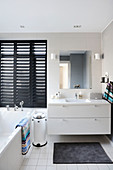 Washstand, black louvre blinds and bathtub in elegant bathroom