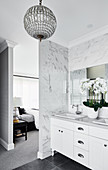 Washstand in ensuite bathroom with marble tiles and crystal lamp