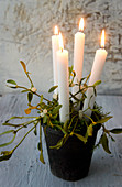 Four white candles in black pot with moss and mistletoe