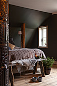 Double bed in rustic attic room with wooden columns, tiled stove and dark walls