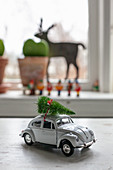 Vintage model car festively decorated with mini Christmas tree on roof