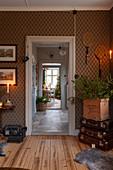 Bilder und Tennisschläger als Wanddeko in Wohnraum mit klassisch gemusterter Wandtapete