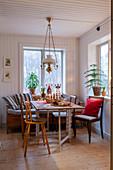 Wooden bench in Scandinavian-style dining area below oil-lamp-style pendant lamp