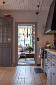 Modern country-house kitchen with blue-grey cupboards, wooden walls and wooden floor