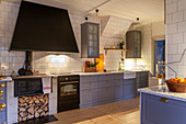 Modern country-house kitchen with blue-grey cupboards, antique wood-fired stove and white-tiled wall