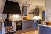 Moderne Landhausküche mit taubenblauen Schrankfronten, antikem Holzofenherd und weißen Fliesenwänden