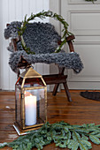 Candle lantern on floor, fir branches, and chair with sheepskin blanket and wreath on veranda