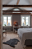 Sheepskin rug on wooden floor of bedroom with double bed and dressing table