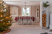 Decorated Christmas tree, stacked firewood and Scandinavian dining area