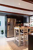Wooden table and barstools in modern kitchen with wood-beamed ceiling