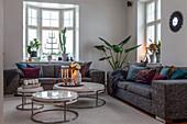 Runde Couchtische im eleganten Wohnzimmer mit Altbaufenstern
