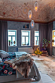Elegant rustic bedroom with mottled painted wall and ornately painted ceiling