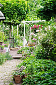 Gepflasterter Weg im Garten mit Rosen und Stauden