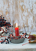 Candle in holder made from cake tin and Virginia creeper berries