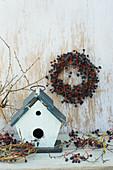 Bird nesting box with wreath of Virginia creeper berries