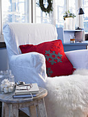 Red cushion with felt appliqué snowflakes on fur blanket on armchair