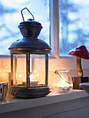 Tealights burning in lantern and candle lantern on windowsill