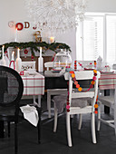 Various chairs around black table with modern Christmas decorations