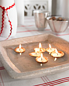 Candles in walnut shells floating in grey dish