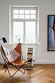 Leseecke am Altbaufenster mit Butterfly Chair, Stehlampe und Bücherstapel