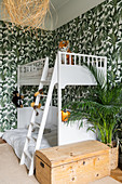White bunk beds in children's bedroom with jungle-patterned wallpaper