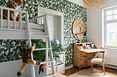 White bunk beds and wooden bureau in children's bedroom with jungle-patterned wallpaper