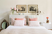 Double bed with white headboard used as shelf and pastel bed linen