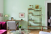 Brass shelves and delicate table in living room with green wall