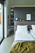 Bed with grey-upholstered headboard against partition wall screening walk-in wardrobe