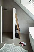 Minimalistisch gehaltenes Bad unter Dachschräge mit Badewanne und ebenerdiger Dusche
