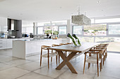 Long dining table in front of modern open-plan kitchen in interior with glass wall
