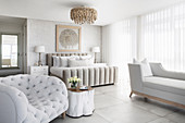 Upholstered furniture in luxurious bedroom in white and pale grey