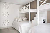 Two sets of bunk beds with steps in beige and white guest bedroom