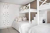Zwei Etagenbetten mit Treppen im Gästezimmer in Beige und Weiß