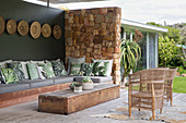 Leaf-patterned scatter cushions on corner sofa on exotic terrace