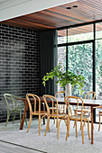 Elongated dining table with bistro chairs in living room with black brick wall