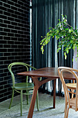 Dining table with bistro chairs in different colors in corner of room against black brick wall