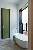 Minimalist bathroom with modern freestanding bathtub and color accents