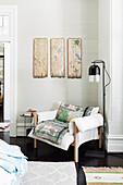 Sitzecke mit antiken handbemalten Wandpaneelen über weißem Polstersessel