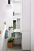 Modern round washbasin on mirrored hanging table in bathroom niche