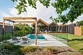 Swimming Pool mit Glasabtrennungen im Garten eines Architektenhauses