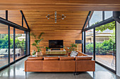 Corner sofa in living room under a pointed roof with double-sided ceiling-high window fronts
