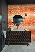 Black vanity with textured front in front of red brick wall in the bathroom