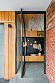 Entrance area with glass swing door and wooden wardrobe with black back wall