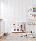 Baby room in bright colors with cot, chest of drawers and wall shelf